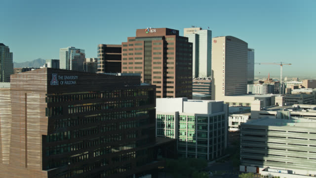 drone flight past the university of arizona college of medicine and other buildings in downtown phoenix - organisation stock videos & royalty-free footage