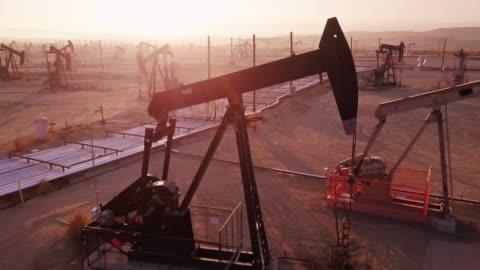 drone flyg förbi arbetar pumpjack i midway-sunset oljefält, kern county, kalifornien - oljepump bildbanksvideor och videomaterial från bakom kulisserna