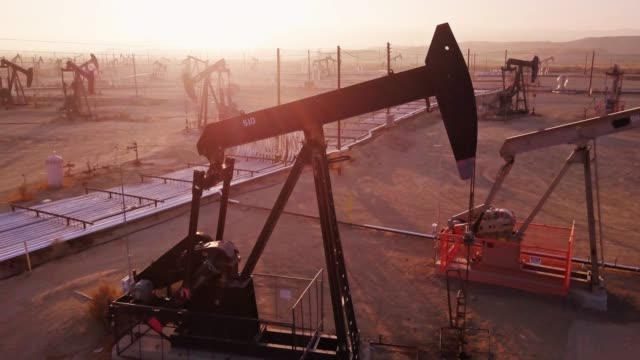 drone flight past working pumpjack in midway-sunset oil field, kern county, california - industria petrolifera video stock e b–roll