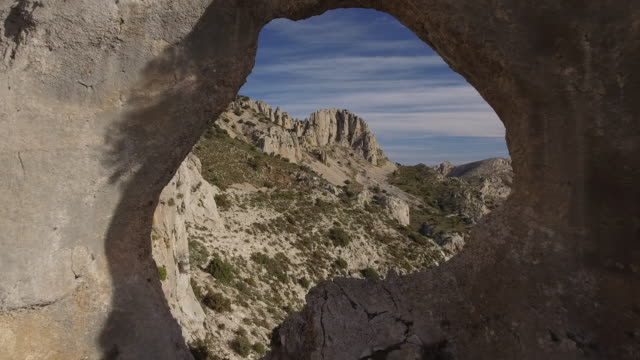 drone flight through a hole in the mountain, similar to the figure of a map of africa - extreme terrain stock videos & royalty-free footage