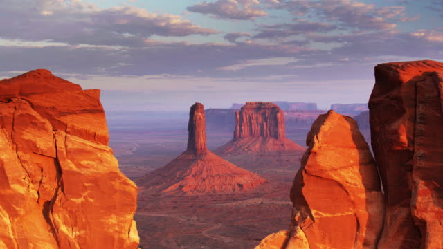 drone flight through notch in sandstone wall towards monument valley buttes - southwest usa stock videos & royalty-free footage