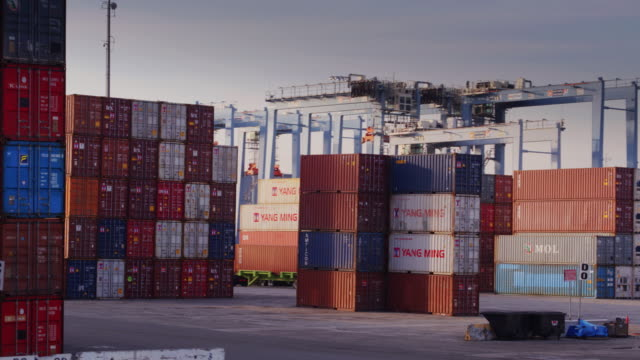 vídeos de stock e filmes b-roll de drone flight through stacked containers in shipping terminal - transporte de mercadoria