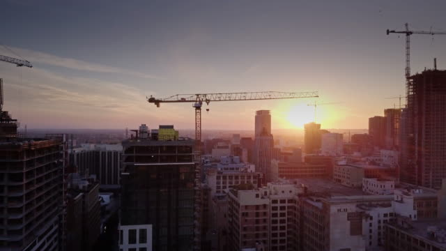 vidéos et rushes de drone flight towards and over a construction crane on a dtla construction site - structure bâtie