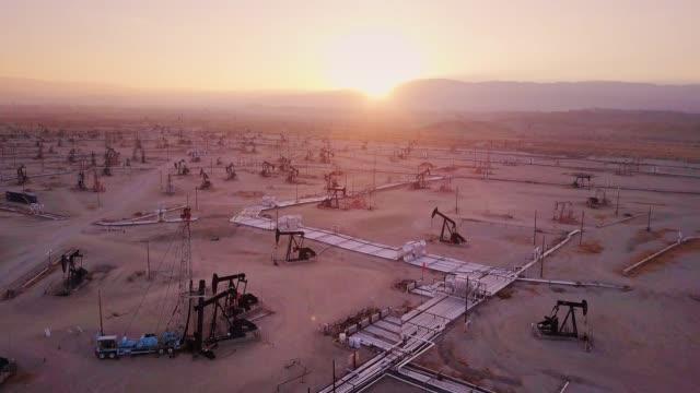 vídeos de stock e filmes b-roll de drone flight towards setting sun with downward tilt over midway-sunset oil field, kern county, california - combustível fóssil