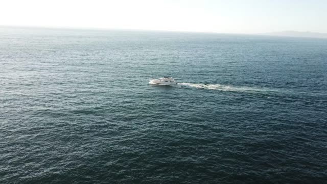 drone flyby of a speeding fishing boat - barca a motore video stock e b–roll