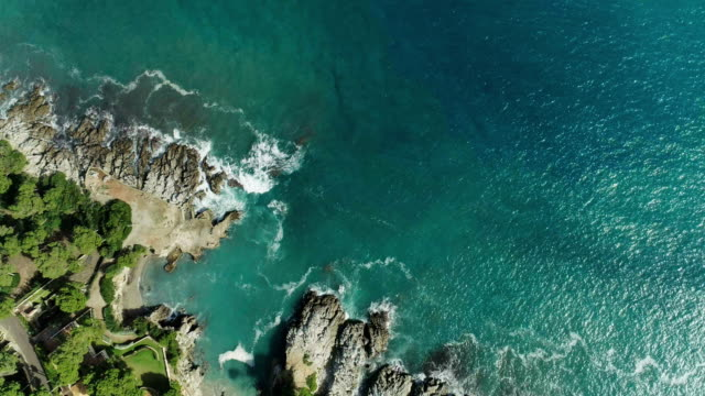 Drone flying above turquoise water. Rocky coastline