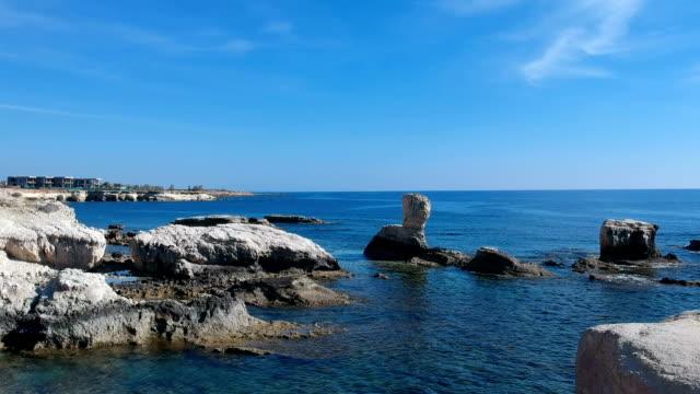 vídeos de stock, filmes e b-roll de drone voando acima da água azul-turquesa. costa rochosa - vista do mar