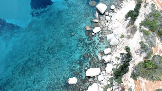 drone flying above turquoise water. rocky coastline - coastal feature stock videos & royalty-free footage
