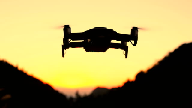 vídeos de stock e filmes b-roll de drone flying against orange sunset - pairar