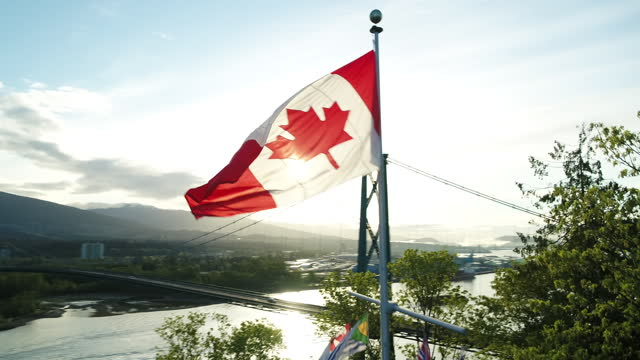 drone flying at prospect point past canada flag with lions gate bridge in background | 4k - canadian flag stock videos & royalty-free footage