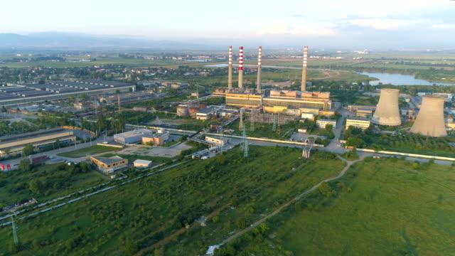 Drohne fliegen weg von Kraftwerk in der Stadt bei Sonnenuntergang