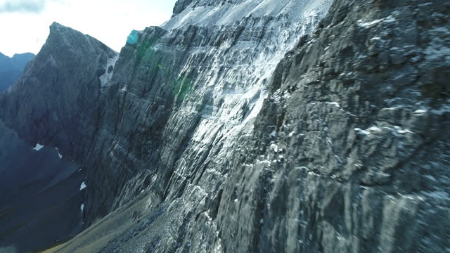 drone flying close to snowy rock cliffs in canadian rocky mountains - mountain range stock videos & royalty-free footage