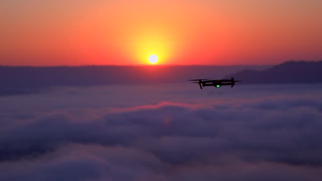 drone flying in silhouette sunset landscape. - quadcopter stock videos & royalty-free footage