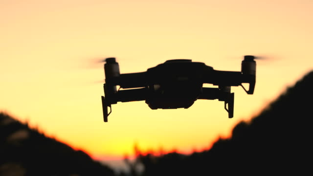 drone flying in the sky at sunset - hovering stock videos & royalty-free footage