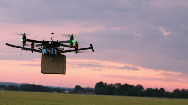 vídeos de stock e filmes b-roll de ls drone flying over fields with a package at dusk - e commerce