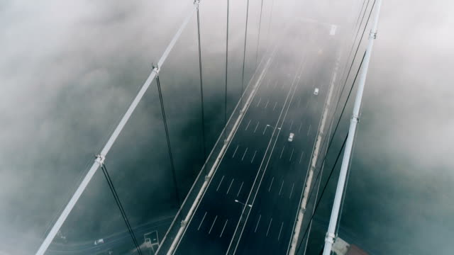 drone flying over foggy bridge at sunrise in istanbul - july 15 martyrs' bridge stock videos & royalty-free footage