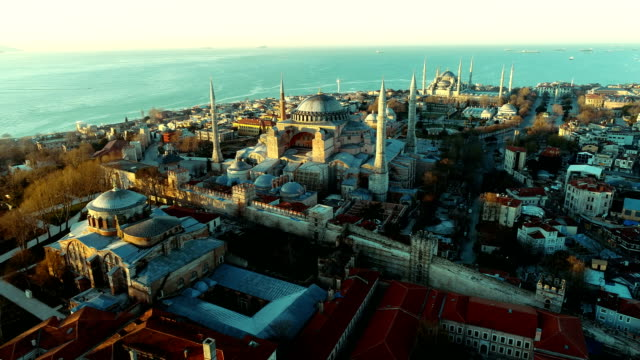 drone flying over hagia sophia and hagia eirene and to blue mosque at sunrise in istanbul - paganism stock videos and b-roll footage