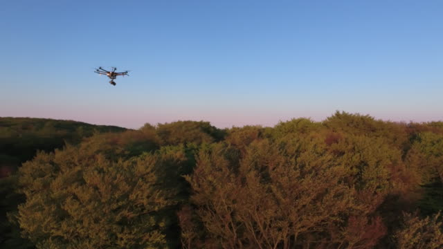 dji s1000 drone flying over landscape at sunset - schwenk stock-videos und b-roll-filmmaterial
