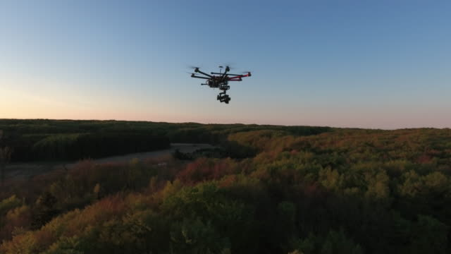 dji s1000 drone flying over landscape at sunset - flying stock videos & royalty-free footage