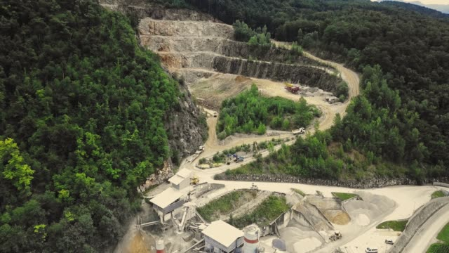 vídeos de stock e filmes b-roll de drone flying over open pit mine/quarry - pedreira