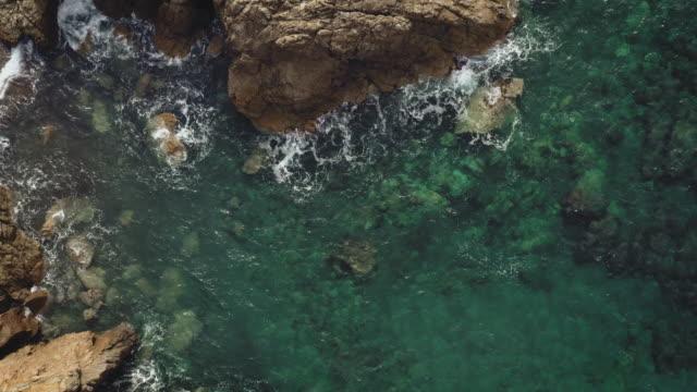 vídeos de stock e filmes b-roll de drone flying over rocky coastline - rebentação