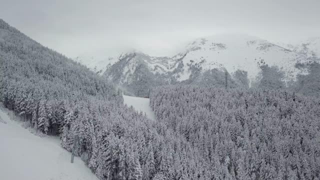 vídeos de stock e filmes b-roll de drone flying over snow covered forest and a ski slope on a mountain - coberto de neve