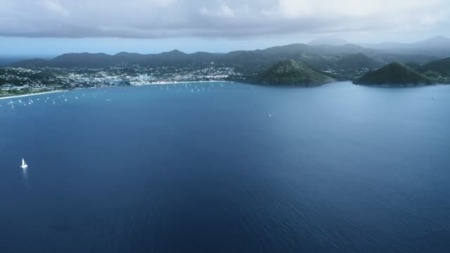 drone flying over the sea with yachts, on the horizon a coastal city, mountains and dense fog (rodney bay, saint lucia) - 船の一部点の映像素材/bロール
