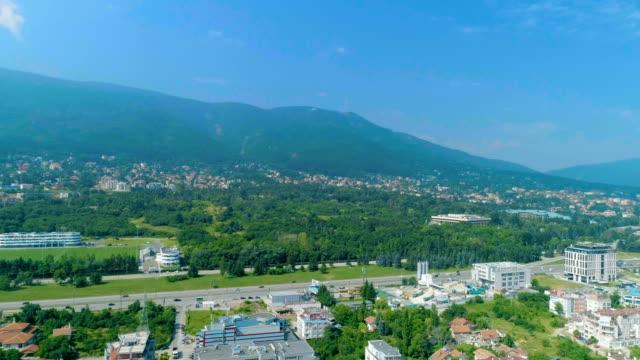 vídeos de stock, filmes e b-roll de drone voando em direção a montanha perto da estrada de cidade grande - bulgária