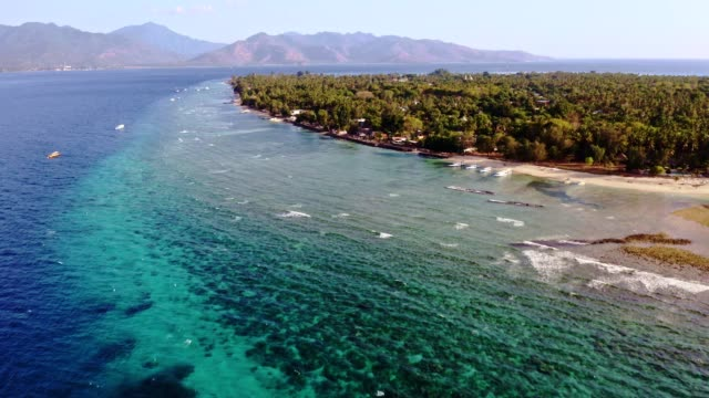 drone flying toward the idyllic gili air island in indonesia - coastline stock videos & royalty-free footage