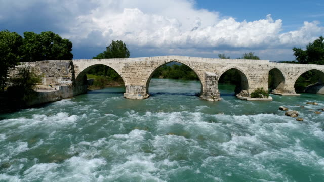 drone flying trough the historical eurymedon bridge in antalya, turkey - arco architettura video stock e b–roll