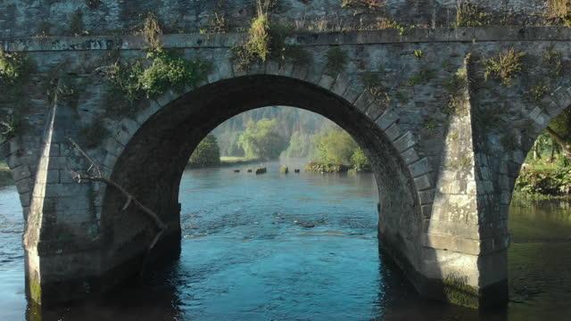 drone pov flying under stone bridge in ireland - arch stock videos & royalty-free footage