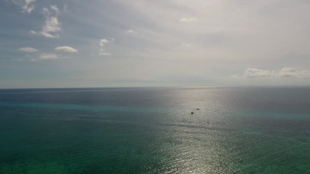 drone flying upwards, over-viewing the caribbean sea and horizon in front of cozumel island. two dive boats are in the water. - sea stock videos & royalty-free footage