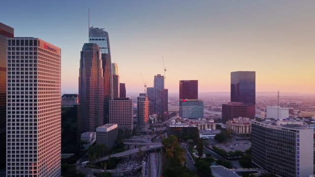 Drone Flyover of Los Angeles Financial District and Freeways at Dusk