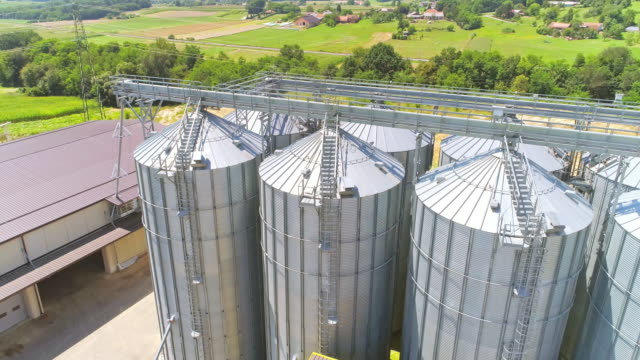aerial drone flyover of silos on wheat farm - storage compartment stock videos and b-roll footage