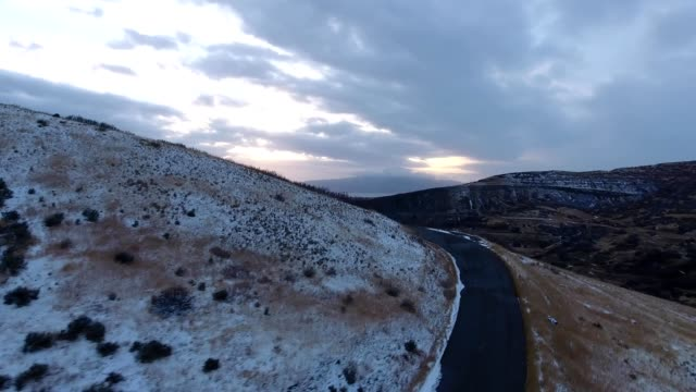 vídeos de stock e filmes b-roll de a drone follow squa peak road by utah valley during winter in provo utah - provo