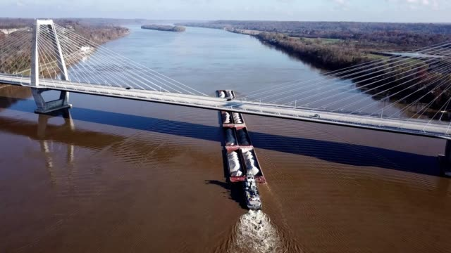 a drone follows a barge being pushed under the lewis and clark bridge in louisville kentucky - barge stock videos & royalty-free footage