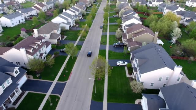 A drone follows a car driving in suburban Oswego Illinois