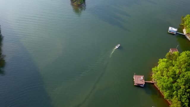 a drone follows a pontoon boat on lake lanier gainesville georgia - anmut stock-videos und b-roll-filmmaterial