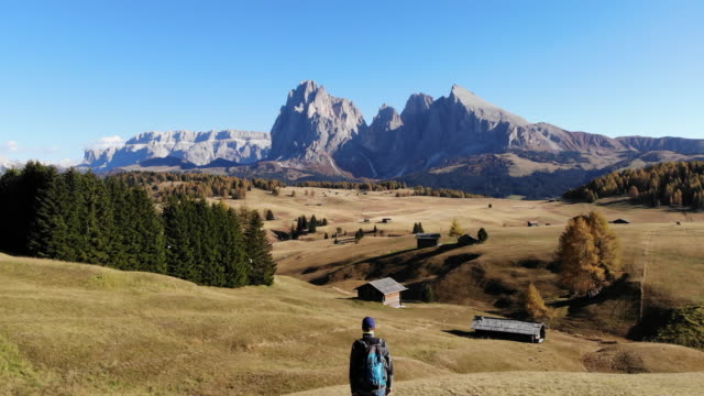 drone footage discovering the beautiful dolomites mountains with meadows and alpine houses in alpe di siusi. - alpe di siusi video stock e b–roll