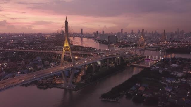 drohne filmmaterial über bhumibol hängebrücke überqueren sie über chao phraya fluss bei sonnenuntergang in bangkok thailand fliegen - bangkok stock-videos und b-roll-filmmaterial