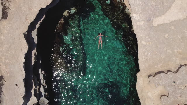 drone footage of a carefree woman floating on her back in the sea - floating on water stock videos & royalty-free footage