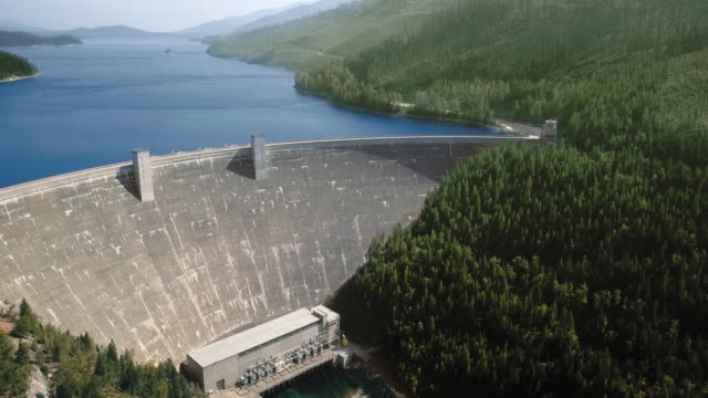 vídeos de stock, filmes e b-roll de drone footage of a dam in front of a calm river between mountains with a dense forest (hungry horse dam, flathead river, montana, usa) - oeste dos estados unidos