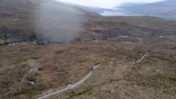Drone footage of a female mountain biker cycling along a mountain bike trail