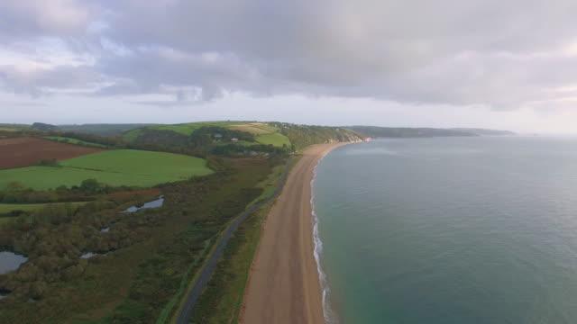drone footage of a highway running along a sandy beach blue ocean in slapton devon uk - road trip stock videos & royalty-free footage
