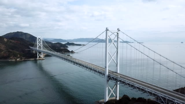 drone footage of a large suspension bridge in japan - hiroshima prefecture stock videos and b-roll footage