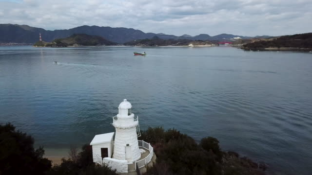 drone footage of a lighthouse and passing boats in western japan - nishiseto expressway stock videos & royalty-free footage