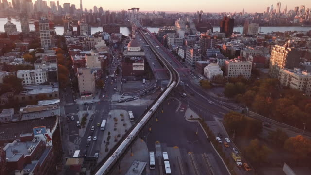 vídeos de stock, filmes e b-roll de drone footage of a nyc subway car passing through williamsburg brooklyn at sunset - williamsburg new york
