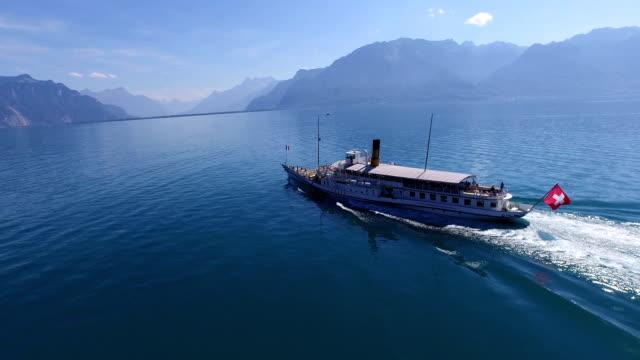 drone footage of a pleasure boat cruising on lake geneva, switzerland - flag stock-videos und b-roll-filmmaterial