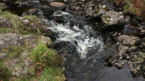 drone footage of a small river flowing over rocks in rural scotland - freshwater stock videos & royalty-free footage