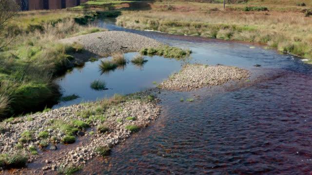 vídeos de stock e filmes b-roll de drone footage of a small river in rural scotland - água doce
